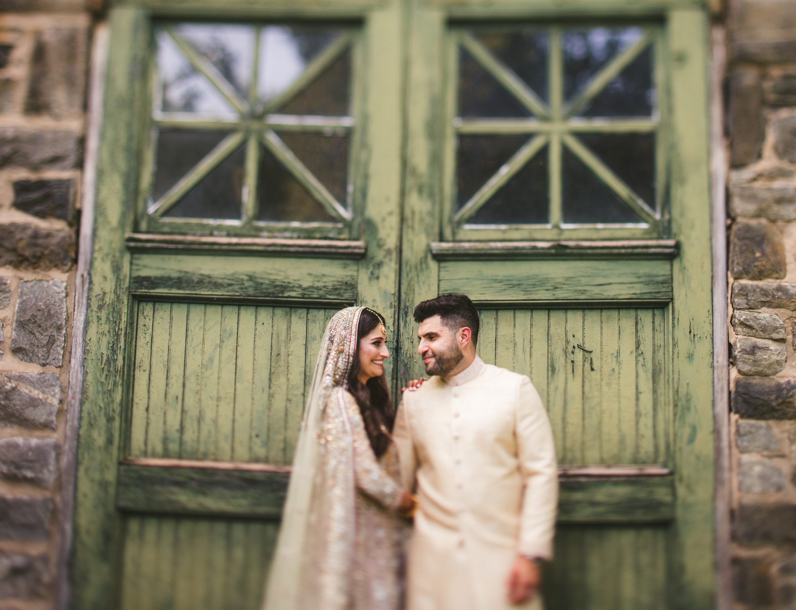 bride and groom in front of green door